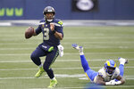 Seattle Seahawks quarterback Russell Wilson (3) scrambles away from Los Angeles Rams outside linebacker Leonard Floyd during the second half of an NFL wild-card playoff football game, Saturday, Jan. 9, 2021, in Seattle. (AP Photo/Ted S. Warren)