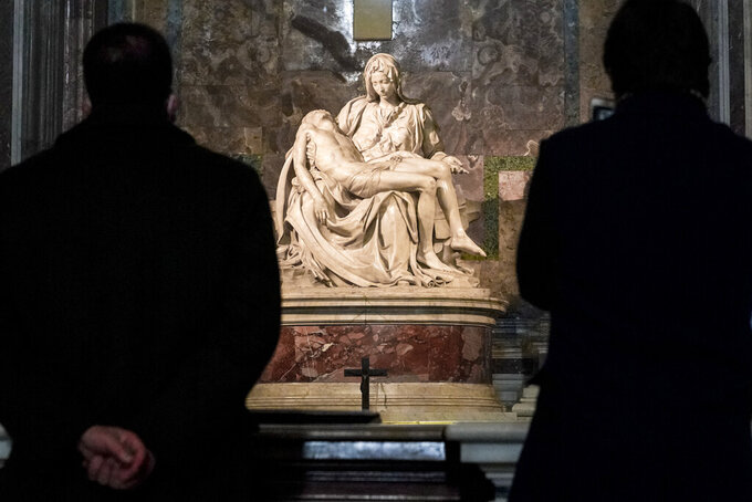 """Visitors admire the marble sculpture """"The Piety"""", made in 1499 by Italian sculptor Michelangelo Buonarroti, inside St. Peter's Basilica, at the Vatican, Monday, Dec. 14, 2020. Like elsewhere in Europe, museums and art galleries in Italy were closed this fall to contain the spread of COVID-19, meaning art lovers must rely on virtual tours to catch a glimpse of the treasures held by famous institutions such as the Uffizi in Florence and the Vatican Museums in Rome. However, some exquisite gems of Italy's cultural heritage remain on display in real life inside the country's churches, some of which have collections of renaissance art and iconography that would be the envy of any museum. (AP Photo/Andrew Medichini)"""