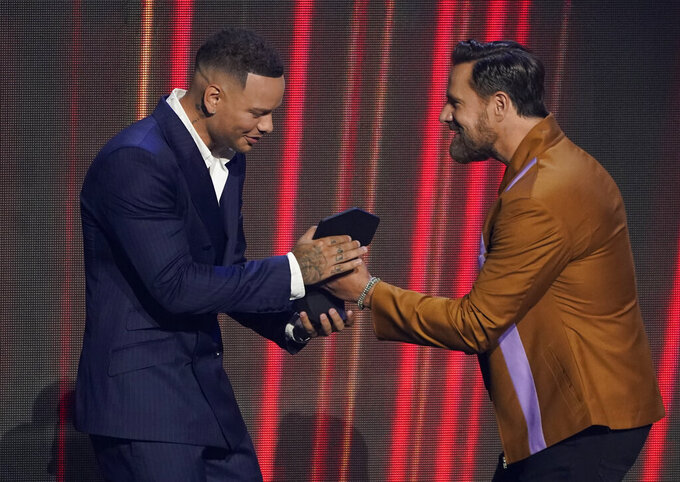 """Jimi Westbrook of Little Big Town, right, presents Kane Brown with the award for male video of the year for """"Worship You"""" at the CMT Music Awards at the Bridgestone Arena on Wednesday, June 9, 2021, in Nashville, Tenn. (AP Photo/Mark Humphrey)"""