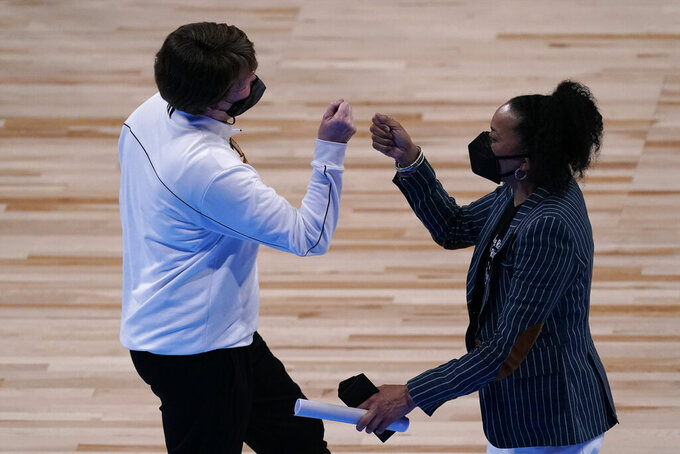 South Carolina head coach Dawn Staley, right, and Mercer head coach Susie Gardner greet each other after their college basketball game in the first round of the women's NCAA tournament at the Alamodome in San Antonio, Sunday, March 21, 2021. South Carolina won 79-53. (AP Photo/Charlie Riedel)