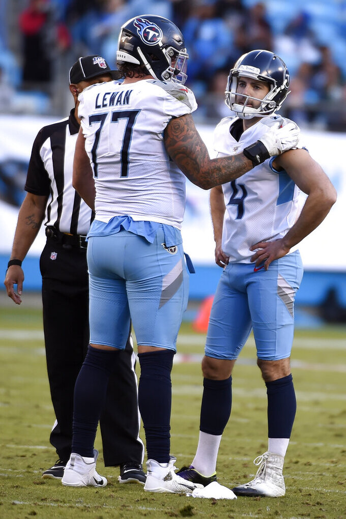 Tennessee Titans offensive tackle Taylor Lewan (77) reacts with kicker Ryan Succop (4) following Succop's missed field goal attempt during the second half of an NFL football game against the Carolina Panthers in Charlotte, N.C., Sunday, Nov. 3, 2019. (AP Photo/Mike McCarn)
