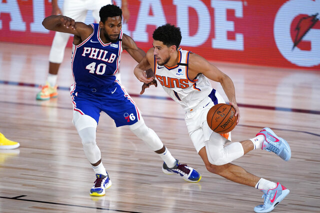 Phoenix Suns guard Devin Booker (1) drives past Philadelphia 76ers forward Glenn Robinson III (40) during the first half of an NBA basketball game Tuesday, Aug. 11, 2020, in Lake Buena Vista, Fla. (AP Photo/Ashley Landis, Pool)