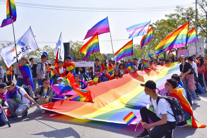 CORRECTS PARTICIPANTS - In this April 15, 2018, photo released by Jiangsu Tongtian Volunteer Group, an LGBT group led more than 100 people in joining a large marathon in the city of Nanjing, holds rainbow flags to raise awareness of LGBT issues. The group had planned to take part the marathon months in advance. Weibo.com, one of China's top social networking sites announced Monday, April 16, 2018 that it will no longer be censoring content related to gay issues after the plan triggered a loud public outcry. (Jiangsu Tongtian Volunteer Group via AP)
