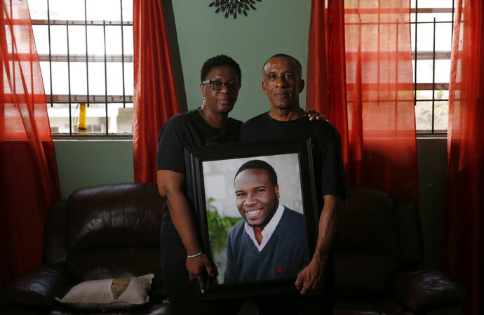 FILE - In this Sept. 25, 2018 file photo, Allison and Bertrum Jean pose as they hold a portrait of their late son Botham Shem Jean at their home in Castries, St. Lucia. A public service announcement honoring the life of Jean, who was killed in his living room by Amber Guyger, a white Dallas police officer who said she mistook his apartment as her own, will air during the Super Bowl next month to highlight the impact of police violence, the family's lawyer said. (Vernon Bryant/The Dallas Morning News via AP, File)