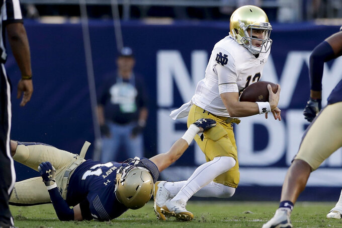 Notre Dame quarterback Ian Book, right, breaks free from Navy linebacker Evan Fochtman, below during the first half of an NCAA college football game against Navy Saturday, Oct. 27, 2018, in San Diego. (AP Photo/Gregory Bull)