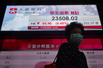 A woman wearing a face mask walks past a bank's electronic board showing the Hong Kong share index at Hong Kong Stock Exchange Wednesday, April 1, 2020. Asian shares were mixed Wednesday, on continuing worries about the economic fallout from the pandemic as reports of coronavirus cases keep surging in various regions. (AP Photo/Vincent Yu)