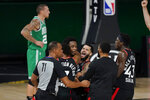 Teammates mob Toronto Raptors' OG Anunoby, second player from left, after Anunoby's game winning shot at the buzzer in the second half of an NBA conference semifinal playoff basketball game against the Boston Celtics Thursday, Sept 3, 2020, in Lake Buena Vista Fla. Celtic's Daniel Theis is at rear. (AP Photo/Mark J. Terrill)