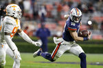 Auburn quarterback Bo Nix (10) scrambles away from Tennessee linebacker Kivon Bennett (95) during the second half of an NCAA college football game Saturday, Nov. 21, 2020, in Auburn, Ala. (AP Photo/Butch Dill)