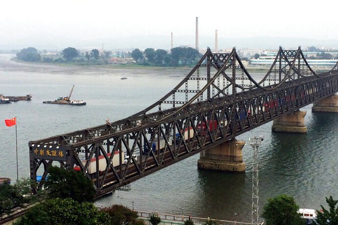 FILE - In this Sept. 4, 2017, file photo, trucks cross the friendship bridge connecting China and North Korea in the Chinese border town of Dandong, opposite side of the North Korean town of Sinuiju.  China's imports from North Korea plunged 92.6 percent in June, 2018, compared with a year earlier under U.N. sanctions imposed to stop Pyongyang's nuclear and missile programs, the customs agency said Friday, July 13, 2018.(AP Photo/Helene Franchineau, File)