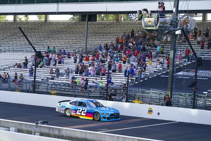 Austin Cindric (22) takes the checkered flag to win a NASCAR Xfinity Series auto race at Indianapolis Motor Speedway in Indianapolis, Saturday, Aug. 14, 2021. (AP Photo/Darron Cummings)