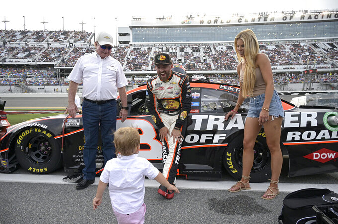 Austin Dillon and his wife Whitney Dillon, right, play with their son, Ace, as car owner Richard Childress, left, watches on pit road before a NASCAR Cup Series auto race at Daytona International Speedway, Saturday, Aug. 28, 2021, in Daytona Beach, Fla. (AP Photo/Phelan M. Ebenhack)