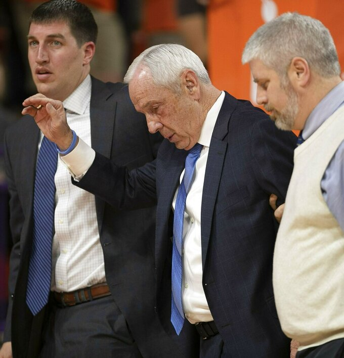 North Carolina coach Roy Williams is escorted off the court and waves, after falling near the bench during the first half of the team's NCAA college basketball game against Clemson on Saturday, March 2, 2019, in Clemson, S.C. (Robert Willett/The News & Observer via AP)