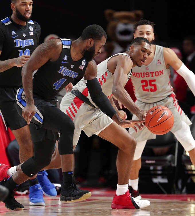 Memphis guard Raynere Thornton (4) has the ball knocked away for a turnover by Houston guard Armoni Brooks (3) during the second half of an NCAA college basketball game Sunday, Jan. 6, 2019, in Houston. (AP Photo/Michael Wyke)