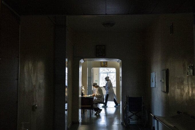 """Olena Obyedko, 26-year-old nurse, wears protective clothing against coronavirus in the hospital for COVID-19 patients in the mining town of Selydove, 700 kilometers (420 miles) east of Kyiv, eastern Ukraine, Thursday, March 4, 2021. Obyedko works in the hospital's intensive-care ward for COVID-19 patients, where people die every week. But, she said, """"I decided not to get vaccinated. I doubt the quality of the vaccine. I'm afraid there will be side effects."""" Ukrainians are becoming increasingly opposed to vaccination: an opinion poll this month by the Kyiv International Institute of Sociology found 60% of the country's people don't want to get vaccinated, up from 40% a month earlier.  (AP Photo/Evgeniy Maloletka)"""