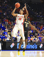 Florida guard Noah Locke (10)  shoots past Towson forward Dennis Tunstall (11) during the first half of an NCAA college basketball game Thursday, Nov. 14, 2019, in Gainesville, Fla. (AP Photo/Matt Stamey)