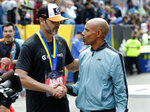 NASCAR driver Jimmie Johnson, left, of Charlotte, shakes hands with grand marshall Meb Keflezighi, of San Diego, after finishing the 123rd Boston Marathon on Monday, April 15, 2019, in Boston. (AP Photo/Winslow Townson)