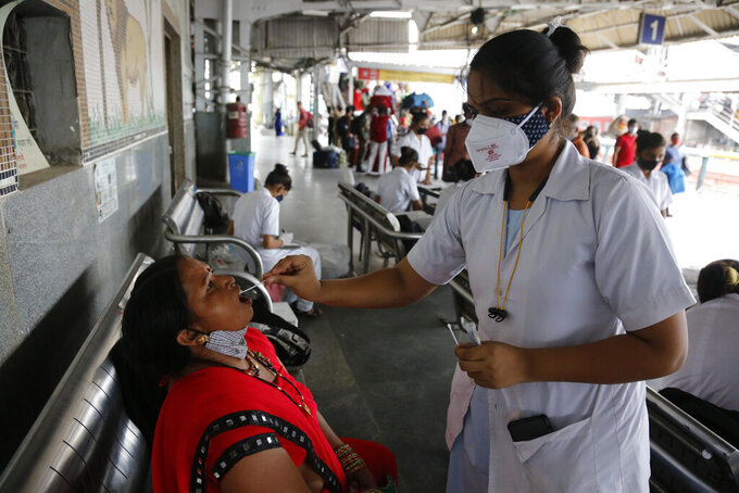 A health worker takes a swab sample of a passenger entering the city to test for COVID-19, at a railway station in Ahmedabad, India, Friday, July 23, 2021. (AP Photo/Ajit Solanki)