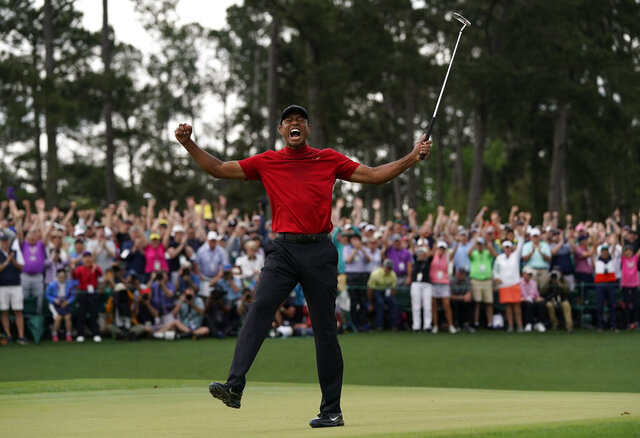 FILE - In this April 14, 2019, file photo, Tiger Woods reacts as he wins the Masters golf tournament in Augusta, Ga. Augusta National decided Friday, March 13, 2020, to postpone the Masters because of the spread of the coronavirus. Club chairman Fred Ridley says he hopes postponing the event puts Augusta National in the best position to host the Masters and its other two events at some later date. Ridley did not say when it would be held. (AP Photo/David J. Phillip, File)