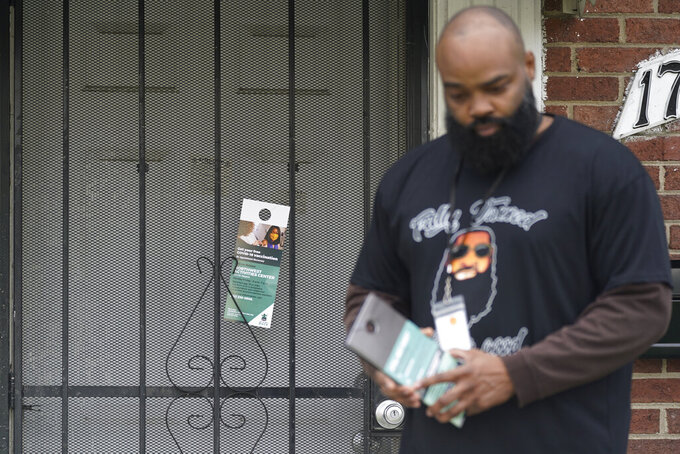 Anthony Brinson leaves a flyer on a home in Detroit, Tuesday, May 4, 2021. Officials are walking door-to-door to encourage residents of the majority Black city to get vaccinated against COVID-19 as the city's immunization rate lags well behind the rest of Michigan and the United States. (AP Photo/Paul Sancya)