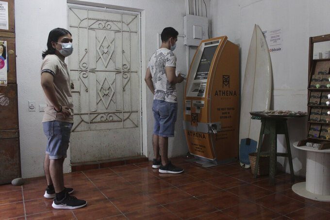 """Eduardo Magaña, right, uses the first ATM designed to withdraw cash through the cryptocurrency App """"Bitcoin Beach"""" on El Zonte Beach in Tamanique, El Salvador, Wednesday, June 9, 2021. In this beach community, a nongovernmental organization with the financial backing of an anonymous Bitcoin donor has been trying to create a small-scale cryptocurrency economy, and could serve as a showcase for the gains and struggles to introduce a phone-based cryptocurrency as the country embarks on a nationwide experiment after making Bitcoin legal tender this week. (AP Photo/Salvador Melendez)"""