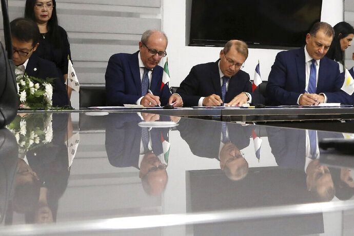 Cyprus' Energy Minister Georgios Lakkotrypis, right, General Manager of Total in Cyprus Yves Grosjean, second right, Manager director of ENI Cyprus Allesandro Barberis, second left, and Director of Kongas Cyprus Insu Woo sign a deal at the Energy ministry in Nicosia, Cyprus, Wednesday, Sept. 18, 2019. Cyprus' energy minister says a consortium made up of energy companies Total of France and Eni of Italy has been granted a license to explore for natural gas deposits in another area off Cyprus' southern coast. (AP Photo/Petros Karadjias)