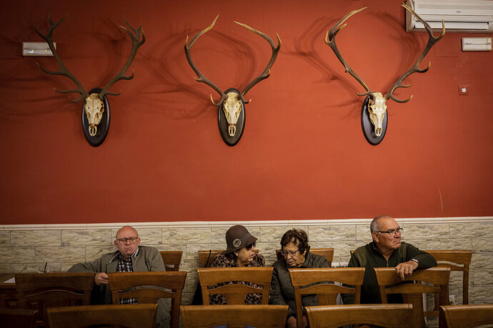 In this April 10, 2019 photo, villagers attend a meeting with Spanish far right party Vox at a bar in Brazatortas, on the edge of the Alcudia valley, central Spain. The April 28 election also comes as Spain's traditional bipartisan politics have crumbled into five main contenders, spurring the race for votes in the overrepresented hinterland, where nearly one third of seats in the parliament's lower house are up for grabs. Following the trotted path of far-right parties elsewhere, Vox is posed to grab 29 to 37 deputies in the national parliament on Sunday, a big splash for a party that only last year made its first big advance with a win in the regional election in Andalusia, a Socialist stronghold. (AP Photo/Bernat Armangue)