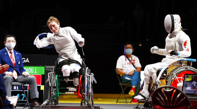 FILE - In this Saturday, Aug. 28, 2021 file photo, Italy's Beatrice Maria Vio, left, celebrates after winning over China's Zhou Jingjing during their the wheelchair fencing women's foil Individual category B gold medal match in Chiba, near Tokyo, at the Tokyo 2020 Paralympic Games, in Tokyo, Japan. When Ursula von der Leyen was lost for words to capture the soul of the European Union and its future on Wednesday, Sept. 15, 2021, Bebe Vio was there to help out the EU's top official at the end of her State of the Union address. Sitting anonymously among the European legislators for most of the hour-long speech which is a highlight on the EU calendar, the Italian Paralympic fencer suddenly became the center of attention when the Commission president called her out as the guest of honor of the august proceedings. (Kyodo News via AP, File)