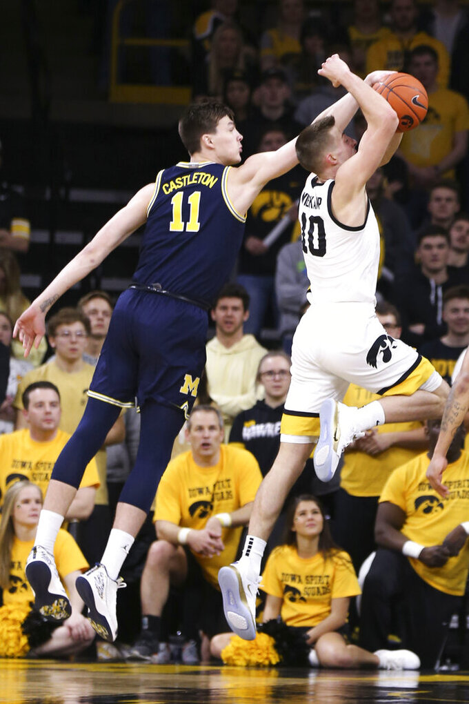 Iowa guard Joe Wieskamp (10) is fouled by Michigan forward Colin Castleton (11) during the first half of an NCAA college basketball game Friday, Jan. 17, 2020, in Iowa City, Iowa. (Rebecca F. Miller/The Gazette via AP)