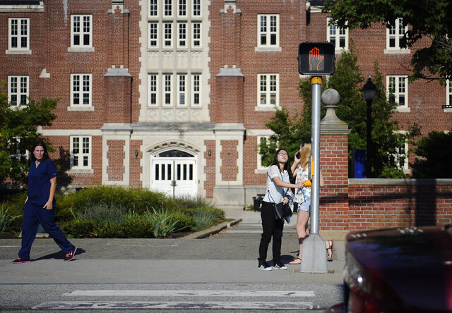 FILE- In this Sept. 18, 2015 file photo, a University of Connecticut student pushes a button at a crosswalk outside one of the student dormitories, in Storrs, Conn. On Friday, Oct. 30, 2020, the university ordered residential students in Storrs to stay away from all off-campus social gatherings until the middle of next week amid a spike in COVID-19 cases. (AP Photo/Jessica Hill, File)
