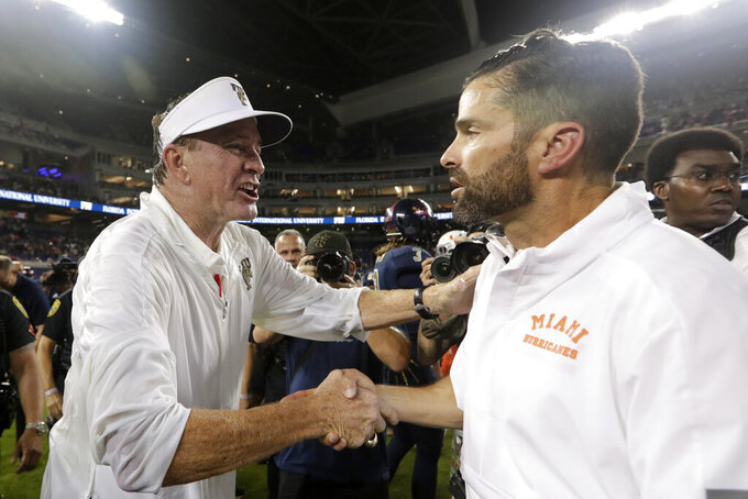 FIU head coach Butch Davis, left, shakes hands with Miami head coach Manny Diaz after an NCAA college football game, Saturday, Nov. 23, 2019, in Miami. FIU won 30-24. (AP Photo/Lynne Sladky)