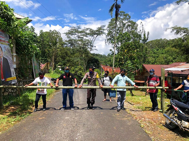 In this April 24, 2020, photo, provided by the Indigenous People Alliance of the Archipelago, indigenous peoples from the Buntao' community in Indonesia's North Toraja regency in South Sulawesi Province use a wooden barrier to block off their village. Indigenous peoples across the archipelago are locking down their villages in an effort to protect their communities from the coronavirus. (AMAN via AP)
