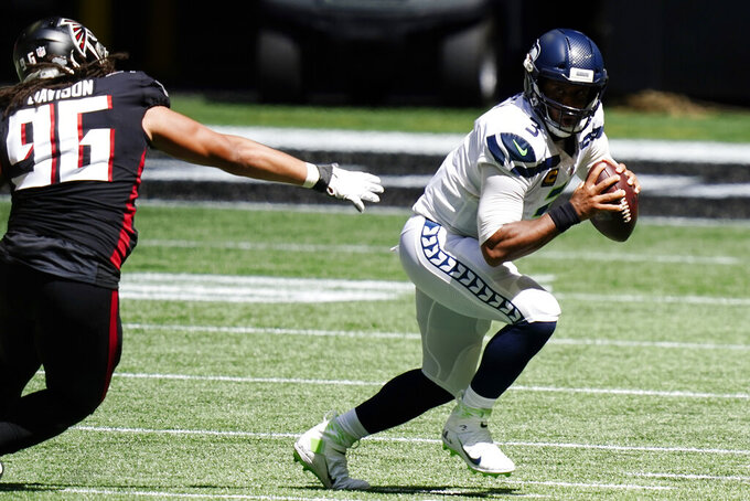 Seattle Seahawks quarterback Russell Wilson (3) runs oput of the pocket against Atlanta Falcons defensive tackle Tyeler Davison (96) during the first half of an NFL football game, Sunday, Sept. 13, 2020, in Atlanta. (AP Photo/Brynn Anderson)