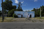 A man rides his bicycle past an abandoned service station in the impoverished east side neighborhood of Saginaw, Mich., on Monday, June 29, 2020. It's difficult to celebrate America in Saginaw this July 4th. The deadly pandemic kept families apart. A brutal recession means money is tight. Weeks of protest over racial inequality left many debating what exactly should be celebrated and what must be changed. (AP Photo/Charles Rex Arbogast)