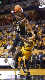 Vanderbilt's Simisola Shittu, left, shoots over Missouri's Xavier Pinson, right, during the first half of an NCAA college basketball game Saturday, Feb. 2, 2019, in Columbia, Mo. (AP Photo/L.G. Patterson)
