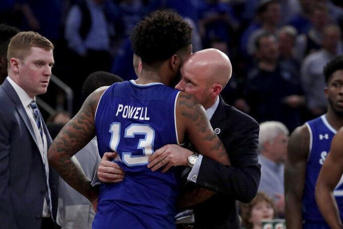 Seton Hall guard Myles Powell, left, is held by head coach Kevin Willard after an argument with Marquette players during the second half of an NCAA college basketball semifinal game in the Big East men's tournament, Friday, March 15, 2019, in New York. Seton Hall won 81-79. (AP Photo/Julio Cortez)
