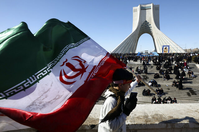 A boy carries an Iranian flag in front of Azadi (Freedom) monument tower in a rally celebrating the 41st anniversary of the Islamic Revolution, in Tehran, Iran, Tuesday, Feb. 11, 2020. Hundreds of thousands across Iran mark the anniversary of the 1979 Islamic Revolution amid some of the highest tensions with Washington in decades while Iran's president denounces America and urges the crowds to vote in parliamentary elections this month.  (AP Photo/Vahid Salemi)