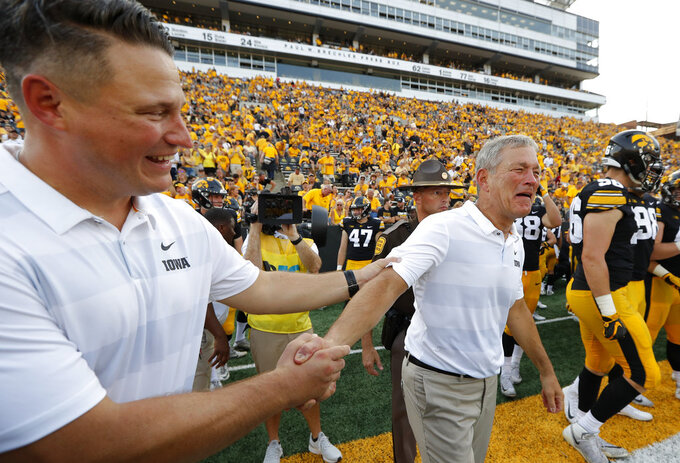Iowa head coach Kirk Ferentz reacts with his son Iowa offensive coordinator Brian Ferentz, left, after an NCAA college football game against Northern Illinois, Saturday, Sept. 1, 2018, in Iowa City, Iowa. Iowa won 33-7 making Kirk Ferentz the winningest coach in Iowa history. (AP Photo/Charlie Neibergall)