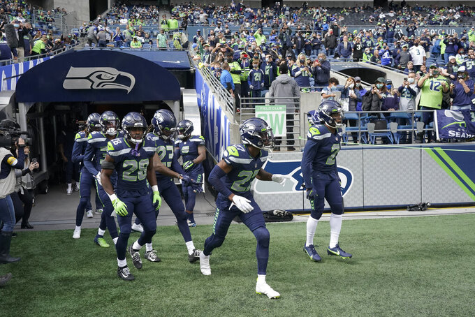 Seattle Seahawks players, including Ugo Amadi (28) and Marquise Blair (27) take the field for warmups before an NFL football game against the Tennessee Titans, Sunday, Sept. 19, 2021, in Seattle. (AP Photo/Elaine Thompson)