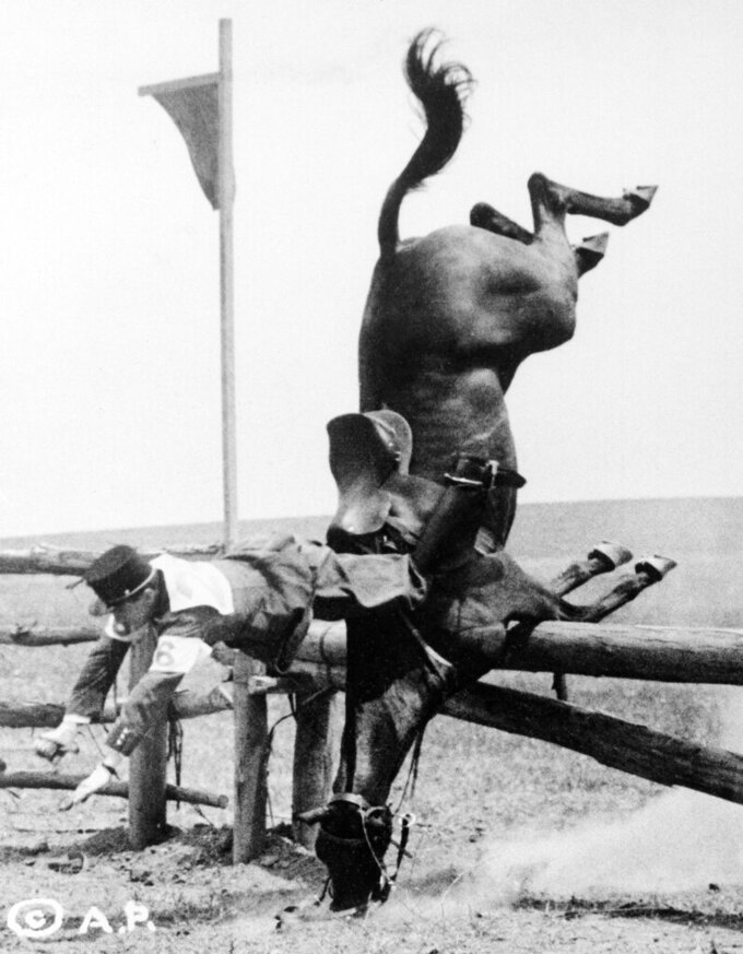 FILE - In this Aug. 2, 1932, file photo, Imre Petnehazy of Hungary, racing a mount strange to him, failed to leap the 14th of 15 jumps in the 5000-meter cross country equestrian event at the Summer Olympics in Los Angeles. Neither rider or mount was seriously injured. (AP Photo/John Thomas Burns, File)