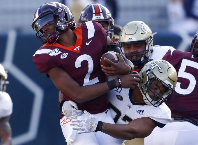 """FILE - In this Saturday, Nov. 16, 2019 file photo, Virginia Tech quarterback Knox Kadum (12) is stopped by Georgia Tech defensive lineman Sylvain Yondjouen of Belgium (32) in the first half of an NCAA football game, in Atlanta. Football in Europe usually means """"soccer."""" But increasingly European kids are excelling at American football. So much so that Europe has become a pipeline of recruits for college football programs — and increasingly for schools from the Power Five conferences. (AP Photo/John Bazemore, file)"""