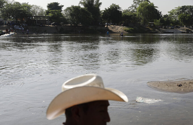 People travel across the Suchiate River from Mexico to Guatemala, the natural border between Guatemala and Mexico, as Mexican immigration agents enforce limits on all but essential travel at its shared border near Ciudad Hidalgo, Mexico, Sunday, March 21, 2021. Mexico wants again to appear cooperative like it was in 2019, when under threat of tariffs from then-President Donald Trump it deployed soldiers to slow down the flow of migrants from Central America, but the reality here is business as usual as entire communities live off migrants headed north for reasons now familiar: violence, an inability to support their families, the devastation wrought by two major hurricanes that hit Central America in November and egged on by rampant misinformation.(AP Photo/Eduardo Verdugo)
