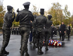 French President Emmanuel Macron inaugurates a memorial for soldiers fallen in foreign conflicts, Monday Nov. 11, 2019 in Paris. As part of commemorations marking 101 years since World War I's Armistice, French President Emmanuel Macron led a ceremony for the 549 French soldiers who died in 17 theaters of conflict since the 60s. The monument memorial depicts six soldiers _ five men and a woman _ holding up an invisible coffin. (Johanna Geron/Pool via AP)