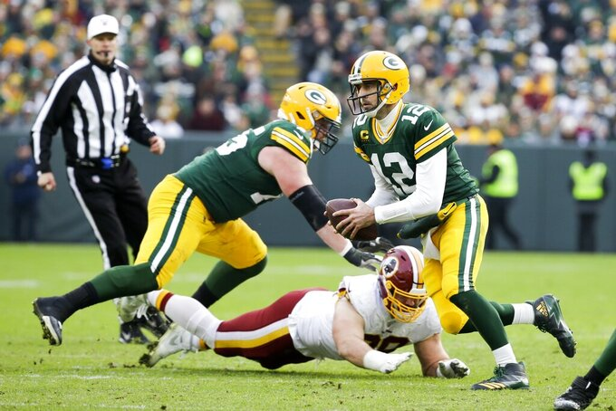 Green Bay Packers' Aaron Rodgers scrambles during the second half of an NFL football game against the Washington Redskins Sunday, Dec. 8, 2019, in Green Bay, Wis. (AP Photo/Mike Roemer)
