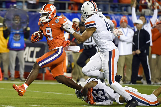 Clemson running back Travis Etienne (9) escapes the tackle attempt by Virginia cornerback Heskin Smith (23) and Virginia linebacker Jordan Mack (4) during the first half of the Atlantic Coast Conference championship NCAA college football game in Charlotte, N.C., Saturday, Dec. 7, 2019. Etienne scored a touchdown on the play. (AP Photo/Mike McCarn)