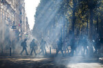 French riot police walk through a tear gas cloud on the Champs Elysees during a yellow vest demonstration, in Paris, Saturday, Sept 21. 2019. Paris police have used tear gas to disperse anti-government demonstrators who try to revive the yellow vest movement in protest at perceived economic injustice and French President Emmanuel Macron's government. The French capital was placed under high alert as few hundred anti-government protesters started marching in the Paris streets. (AP Photo/Kamil Zihnioglu)