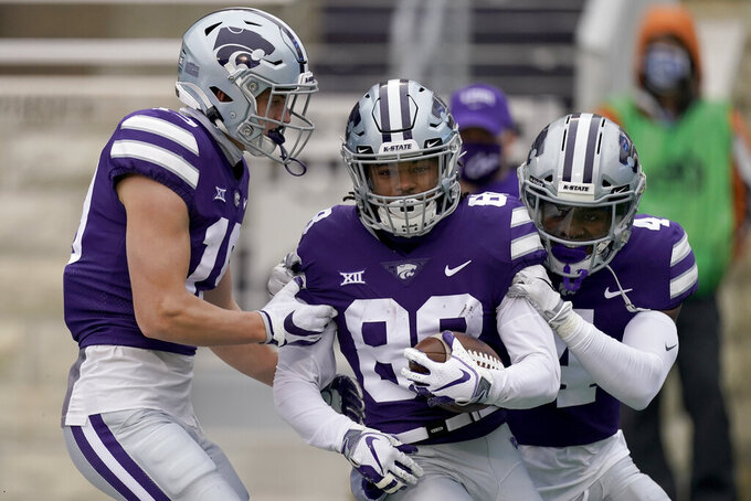 Kansas State wide receiver Phillip Brooks (88) celebrates with wide receiver Malik Knowles (4) and tight end Samuel Wheeler, left, after scoring a touchdown during the first half of an NCAA football game against Kansas Saturday, Oct. 24, 2020, in Manhattan, Kan. (AP Photo/Charlie Riedel)