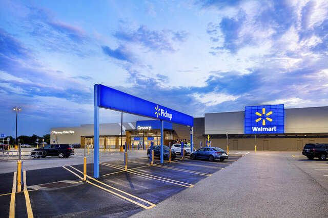 This July 2020 photo provided by Walmart shows the bright signage and Walmart logos from the parking lot outside the Walmart Supercenter in Springdale, Ark. Walmart is getting inspiration from the airport terminal as it revamps the layout and signage of its stores to speed up shopping and better cater to smartphone-armed customers. (Mark Steele + FITCH/Courtesy of Walmart via AP)