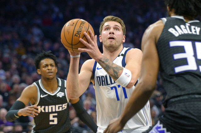 Dallas Mavericks forward Luka Doncic (77) drives to the basket past Sacramento Kings guard De'Aaron Fox (5) and forward Marvin Bagley III (35) during the first quarter of an NBA basketball game in Sacramento, Calif., Wednesday, Jan. 15, 2020. (AP Photo/Randall Benton)