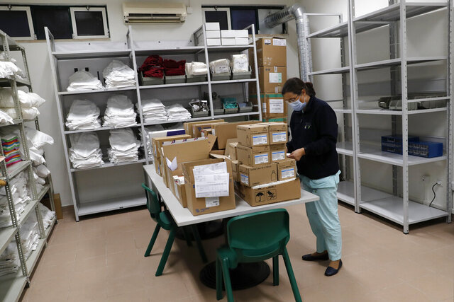 A nurse sorts pharmacy supplies just delivered at a new field hospital set up in a sports hall in Lisbon, Wednesday, Jan. 20, 2021. Portugal's new daily COVID-19 cases have jumped to more than 14,600 to set a new national record. The pandemic has gained momentum in Portugal since Christmas, when restrictions on gatherings and movement were eased for four days. (AP Photo/Armando Franca)