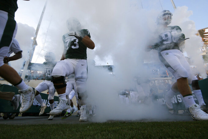 Michigan State players run onto the field before an NCAA college football game against Utah State, Friday, Aug. 31, 2018, in East Lansing, Mich. (AP Photo/Al Goldis)